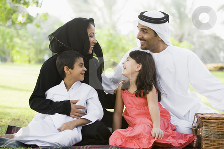A Middle Eastern family sitting in a park stock photo,  by Monkey Business Images