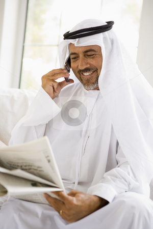 A Middle Eastern man talking on a mobile phone while reading a n stock photo,  by Monkey Business Images