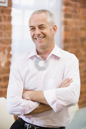 Businessman sitting in office space smiling stock photo,  by Monkey Business Images