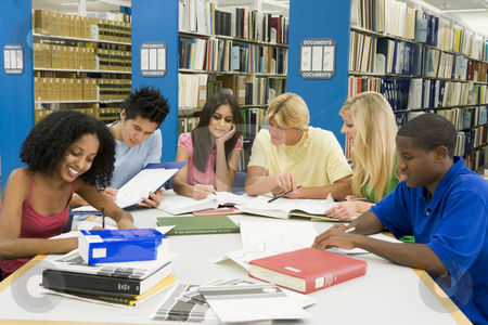 Group of university students working in library stock photo, Group of six students working around table in library by Monkey Business Images