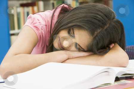 Exhausted university student in library stock photo, Tired female student sleeping at desk by Monkey Business Images