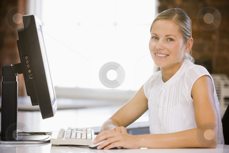 Businesswoman sitting in office with computer smiling stock photo,  by Monkey Business Images