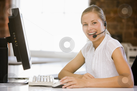 Businesswoman wearing headset sitting in office smiling stock photo,  by Monkey Business Images
