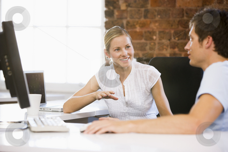 Two businesspeople in office talking and smiling stock photo,  by Monkey Business Images