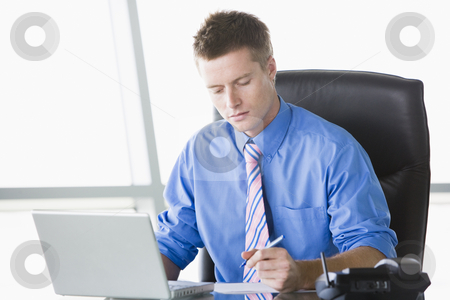 Businessman sitting in office with laptop writing note stock photo,  by Monkey Business Images