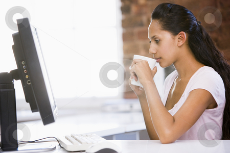 Businesswoman in office drinking coffee and looking at computer stock photo,  by Monkey Business Images