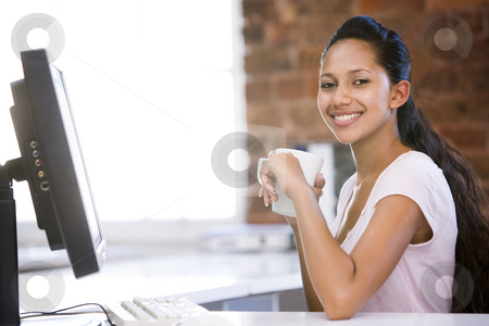 Businesswoman in office drinking coffee and smiling stock photo,  by Monkey Business Images