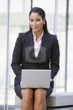 Businesswoman using laptop computer outside stock photo, Businesswoman using laptop computer outside by Monkey Business Images