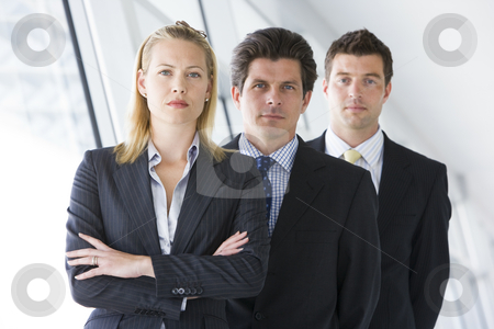 Three businesspeople standing in corridor stock photo,  by Monkey Business Images