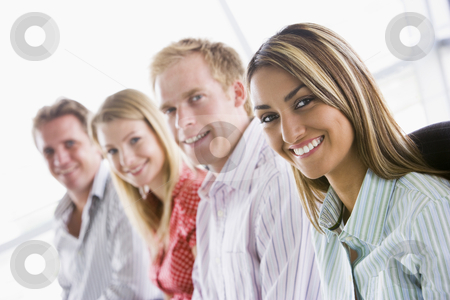 Four businesspeople sitting indoors smiling stock photo,  by Monkey Business Images