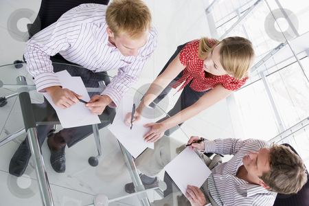 Three businesspeople in boardroom with paperwork stock photo,  by Monkey Business Images