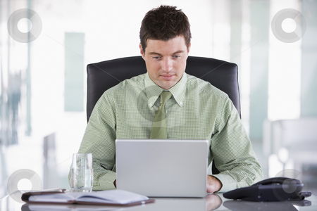 Businessman sitting in office with personal organizer and laptop stock photo,  by Monkey Business Images