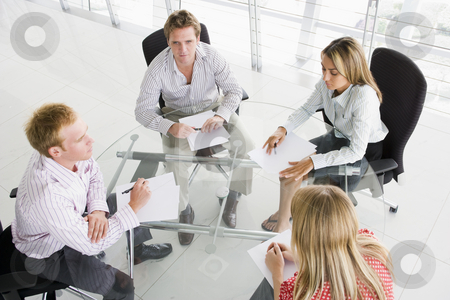 Four businesspeople in boardroom with paperwork stock photo,  by Monkey Business Images
