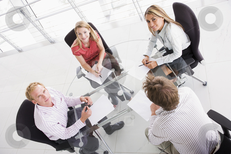 Four businesspeople in boardroom with paperwork smiling stock photo,  by Monkey Business Images