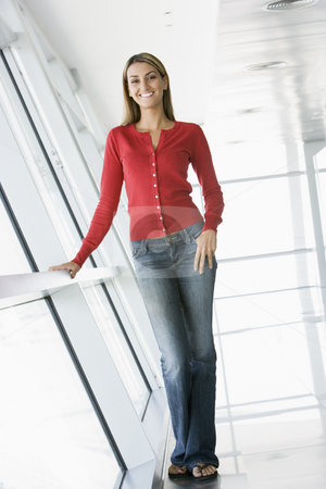 Woman standing in corridor smiling stock photo,  by Monkey Business Images