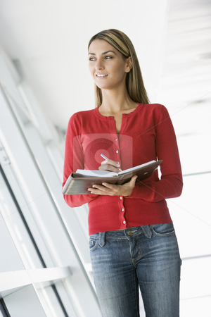 Woman standing in corridor writing in personal organizer stock photo,  by Monkey Business Images