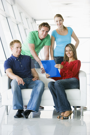 Four people in lobby pointing at clipboard smiling stock photo,  by Monkey Business Images