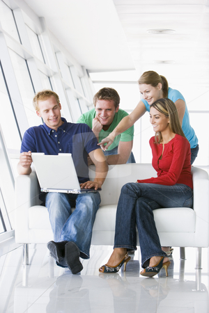 Four people in lobby pointing at laptop smiling stock photo,  by Monkey Business Images