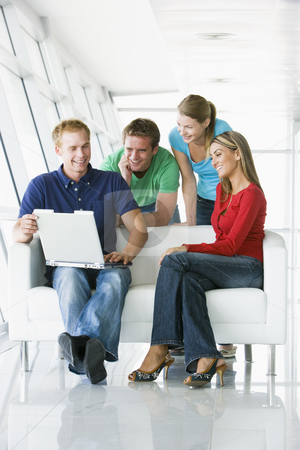 Four people in lobby looking at laptop smiling stock photo,  by Monkey Business Images