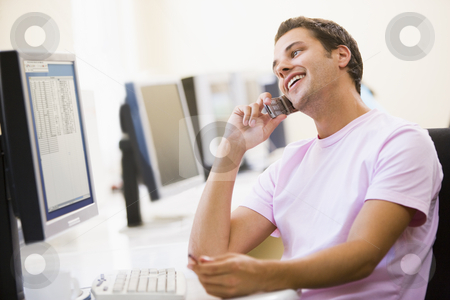 Man sitting in computer room using cellular phone and smiling stock photo,  by Monkey Business Images