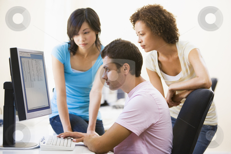 Three people sitting in computer room looking at monitor stock photo,  by Monkey Business Images