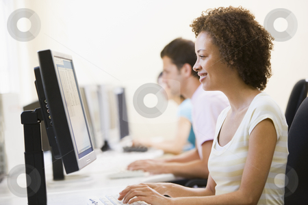 Three people sitting in computer room typing and smiling stock photo,  by Monkey Business Images