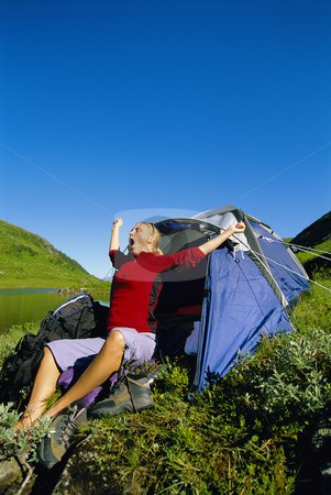 Young woman waking up next to tent stock photo,  by Monkey Business Images