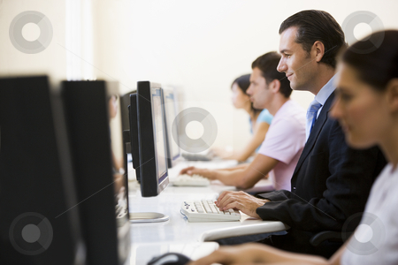 Four people sitting in computer room typing with one man in a su stock photo,  by Monkey Business Images