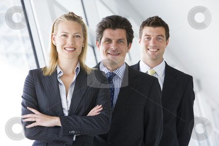 Three businesspeople standing in corridor smiling stock photo,  by Monkey Business Images