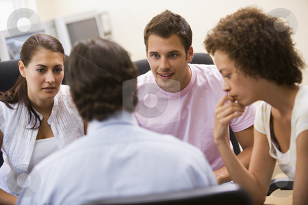 Man giving lecture to three people in computer room stock photo,  by Monkey Business Images