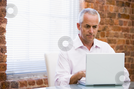 Businessman in office looking at laptop stock photo,  by Monkey Business Images