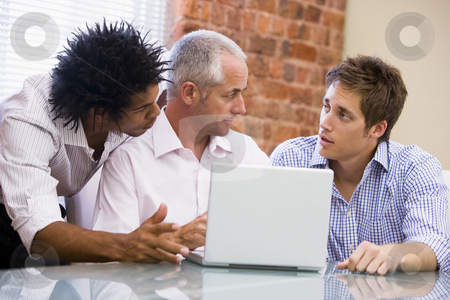 Three businessmen in office with laptop talking stock photo,  by Monkey Business Images