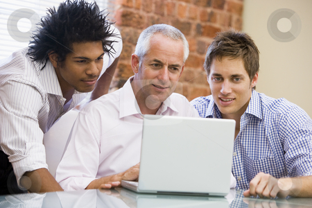 Three businessmen in office looking at laptop smiling stock photo,  by Monkey Business Images