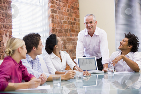 Five businesspeople in boardroom with laptop laughing stock photo,  by Monkey Business Images