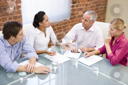 Four businesspeople in boardroom meeting stock photo,  by Monkey Business Images
