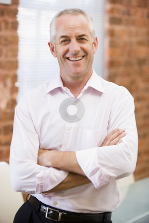 Businessman standing in office laughing stock photo,  by Monkey Business Images