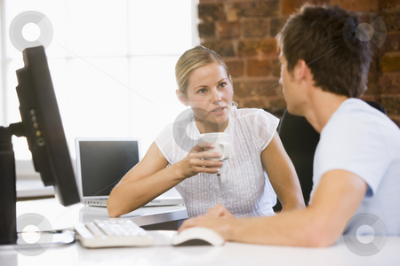 Two businesspeople in office drinking coffee and talking stock photo,  by Monkey Business Images