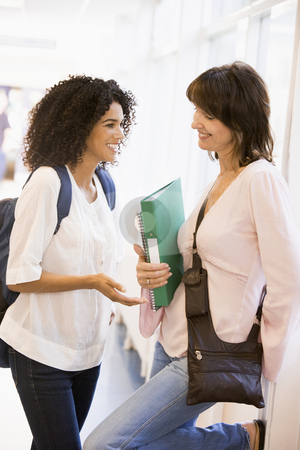 Two women students chatting in a campus corridor stock photo,  by Monkey Business Images