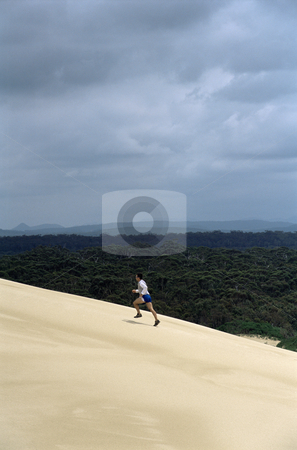 Man running up sand dune stock photo,  by Monkey Business Images