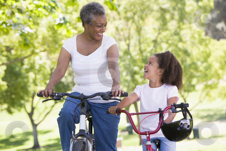 Grandmother and granddaughter on bikes outdoors smiling stock photo,  by Monkey Business Images