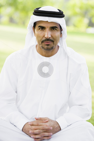 A Middle Eastern man sitting in a park stock photo,  by Monkey Business Images