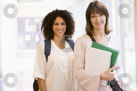 Two women with backpacks standing in a campus corridor stock photo,  by Monkey Business Images