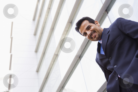 Businessman standing outside office building stock photo, Businessman standing outside modern office building by Monkey Business Images