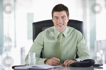 Businessman sitting in office with personal organizer smiling stock photo,  by Monkey Business Images