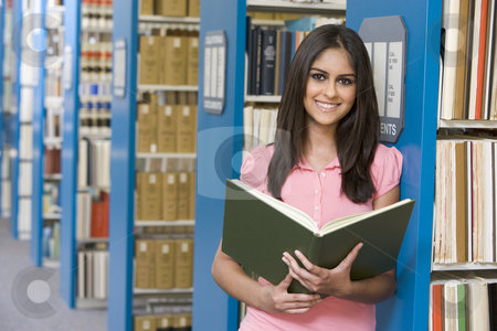 University student in library stock photo, University student studying in library holding book by Monkey Business Images