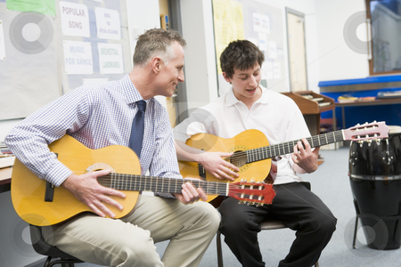 Schoolboy and teacher playing guitar in music class stock photo,  by Monkey Business Images