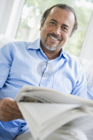 A Middle Eastern man reading a newspaper at home stock photo,  by Monkey Business Images