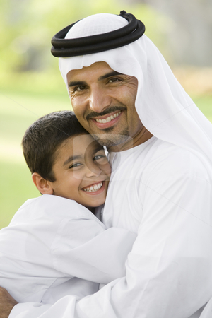 A Middle Eastern man and his son sitting in a park stock photo,  by Monkey Business Images
