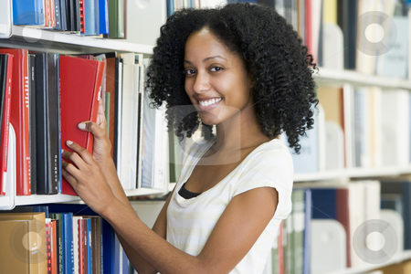 University student selecting book in library stock photo, Female university student selecting library book from shelf by Monkey Business Images