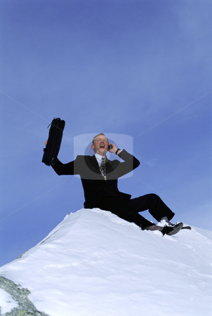 Businessman outdoors on snowy mountain using cellular phone and  stock photo,  by Monkey Business Images